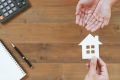 Bästa sikt av händer som ger huspapper för att skydda med räknemaskinen, Arkivfoton