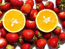 Bästa sikt av halvan av apelsinen som omges av röda jordgubbar på vit bakgrund arkivfoton