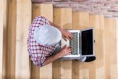 Bästa sikt av hipsteren som arbetar på bärbara datorn och inomhus sitter på trappa royaltyfri fotografi