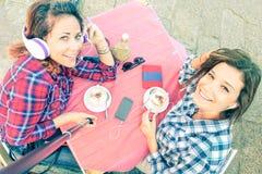Bästa sikt av hipsterflickvänner som tar selfie på cappuccinostången arkivfoton