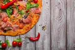 Bästa sikt av italiensk pizza på en lantlig tabellbakgrund Ett stycke av salamipizza med körsbärsröda tomater och varm chili Royaltyfria Foton