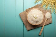 Bästa sikt av jasminris med jasminblomman överst i en träbunke, sked och öra av ris royaltyfria bilder