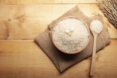 Bästa sikt av jasminris med jasminblomman överst i en träbunke, skedsäckvävsäck och öra av ris med träbakgrund royaltyfria bilder