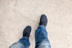 Bästa sikt av jeans för mankläder och svarta gymnastikskor Royaltyfri Foto
