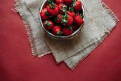 Bästa sikt av jordgubbar i bunke på röd bakgrundsbukett av pioner Royaltyfria Foton