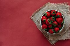 Bästa sikt av jordgubbar i bunke på röd bakgrundsbukett av pioner Royaltyfria Bilder