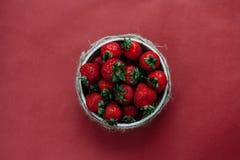 Bästa sikt av jordgubbar i bunke på röd bakgrundsbukett av pioner Royaltyfri Fotografi