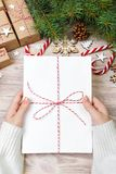 Bästa sikt av julbokstaven i hand Stäng sig upp av händer som rymmer tom wishlist på trätabellen med xmas-garnering arkivbild