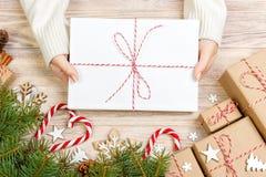 Bästa sikt av julbokstaven i hand Stäng sig upp av händer som rymmer tom wishlist på trätabellen med xmas-garnering royaltyfri fotografi