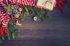 Bästa sikt av julgarnering - den röda bunken mycket av gran-kottar, gåvaasken som slås in i kraft papper, guld- ängel, sörjer fil Royaltyfri Foto