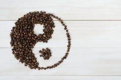 Bästa sikt av kaffebönor som gör ett symbol Yin yang på ljus träyttersida arkivbilder