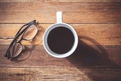 Bästa sikt av kaffekoppen med exponeringsglas på trätabellbakgrund Arkivfoton