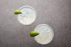 bästa sikt av kalla alkoholmargaritacoctailar med stycken av limefrukt på den gråa tabletopen fotografering för bildbyråer