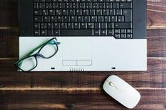 Bästa sikt av kontorsmaterial med musen och monokeln för bärbar dator den trådlösa Royaltyfria Bilder
