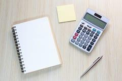 Bästa sikt av kontorsskrivbordet med anteckningsboken, räknemaskinen, pennan och anmärkningen Royaltyfri Bild