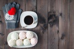 Bästa sikt av koppen av svart kaffe med handskar på träbackgroun arkivbilder