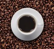 Bästa sikt av koppen av varmt kaffe på stekkaffebönan Sikt för fågelögon av kaffekoppen på rå kaffebönor Royaltyfria Foton