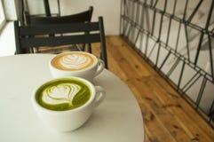 Bästa sikt av koppen av matchate och cappuccino royaltyfri bild