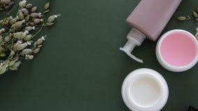 Bästa sikt av kosmetiska produkter och lösa blommor på djupt - grön bakgrund Wellnessskönhetbehandling stock video
