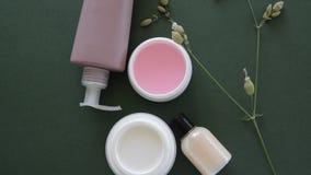 Bästa sikt av kosmetiska produkter och lösa blommor på djupt - grön bakgrund Wellnessskönhetbehandling arkivfilmer