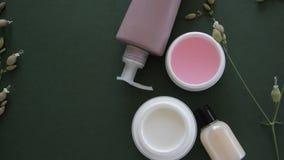 Bästa sikt av kosmetiska produkter och lösa blommor på djupt - grön bakgrund Wellnessskönhetbehandling lager videofilmer