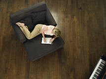 Bästa sikt av kvinnahandstil i anteckningsbok på soffan Arkivfoto