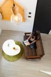Bästa sikt av kvinnaläseboken och sammanträde på soffan arkivbilder