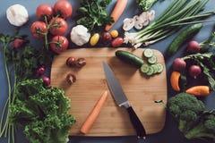 Bästa sikt av kvinnan som lagar mat sund mat: ingred bitande grönsak Royaltyfri Fotografi