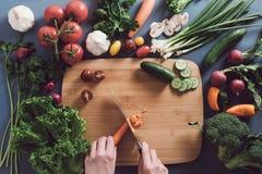 Bästa sikt av kvinnan som lagar mat sund mat: ingred bitande grönsak Arkivbilder