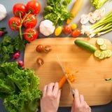 Bästa sikt av kvinnan som lagar mat sund mat: ingred bitande grönsak Royaltyfria Foton