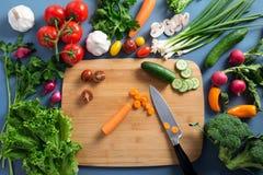 Bästa sikt av kvinnan som lagar mat sund mat: ingred bitande grönsak Arkivbild