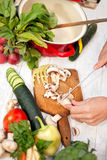 Bästa sikt av kvinnan som skivar champignons med en kniv Arkivfoto