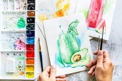 Bästa sikt av kvinnliga händer som drar avokadosmoothien med den vattenfärgmålarfärger och målarpenseln på trätabellen stock illustrationer