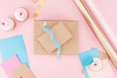 Bästa sikt av läckra muffin, tomma kort, bandet, inpackningspapper och den packade upp gåvaasken på rosa färger Royaltyfria Bilder