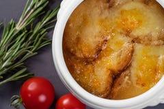 Bästa sikt av lök-ost soppa med krutonger Tjänat som i en vit kruka på en grå bakgrund Arkivfoton