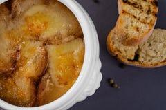 Bästa sikt av lök-ost soppa med krutonger Tjänat som i en vit kruka på en grå bakgrund Royaltyfri Foto