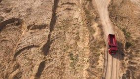 Bästa sikt av lastbilen som kör på den lantliga vägen plats Dumperritter på den torra gula villebrådvägen i sommar Tungt maskiner arkivbild