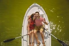 Bästa sikt av lyckliga älska par som ror ett litet fartyg på en sjö Ett roligt datum i natur Par som kramar i ett fartyg Arkivfoto