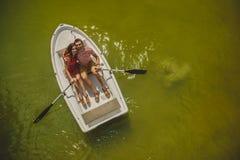 Bästa sikt av lyckliga älska par som ror ett litet fartyg på en sjö Ett roligt datum i natur Par som kramar i ett fartyg Arkivbilder