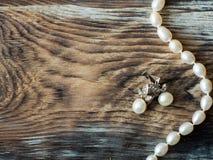 Bästa sikt av lyxpärlahalsbandet och pärlaörhängen på den gamla trätabellen med kopieringsutrymme upp Royaltyfria Bilder