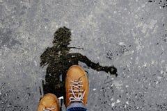 Bästa sikt av mannen som går på den våta jordningen efter stoppat ha regnat Arkivfoton