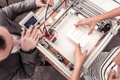 Bästa sikt av mannen som justerar skrivaren 3D royaltyfria bilder
