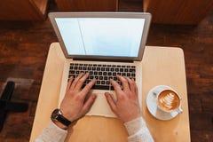 Bästa sikt av mansammanträde i kafé, medan genom att använda bärbara datorn Royaltyfria Bilder