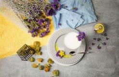 Bästa sikt av milkshake i ett exponeringsglas En platta med en mjölkaktig efterrätt, exotiska frukter och gulliga blommor på en f royaltyfri bild