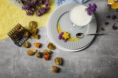 Bästa sikt av milkshake i ett exponeringsglas En platta med en mjölkaktig efterrätt, exotiska frukter och gulliga blommor på en f arkivfoton