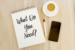 Bästa sikt av mobiltelefonen, pennan, en kopp kaffe och anteckningsboken som är skriftlig med fråga vad dig behöver? Affärs- och  royaltyfri fotografi