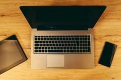 Bästa sikt av moderna trådlösa elektroniska apparater på kontorstabellen Arkivfoto
