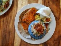 Bästa sikt av Nasi Kerabu eller Nasi Ulam, blå färgrissallad, traditionell malaysian kokkonst på trätabellen arkivfoton