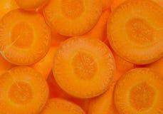 Bästa sikt av ny orange morotskivabakgrund arkivfoto