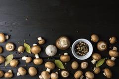 Bästa sikt av nya champinjoner med den pepparkornblandningen och lagerbladen på arkivbild